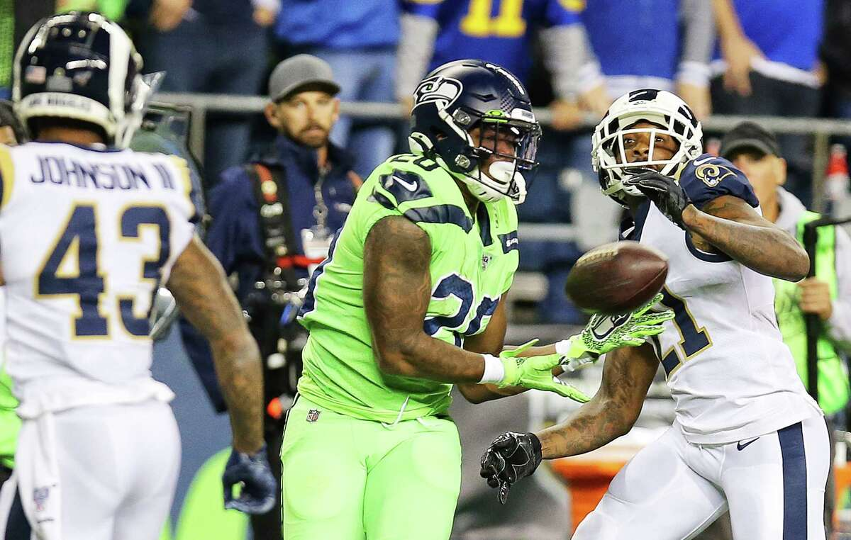 Seattle Seahawks running back Rashaad Penny (20) makes a 30 yard catch between Los Angeles Rams strong safety John Johnson (43) and Rams cornerback Aqib Talib (21) in the third quarter of Seattle's game against the LA Rams, Thursday, Oct. 3, 2019.