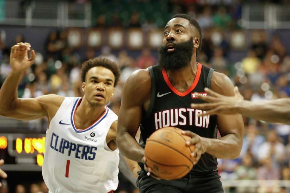 Houston Rockets shooting guard James Harden (13) gets by Los Angeles Clippers shooting guard Jerome Robinson (1) during the first quarter of an NBA preseason basketball game, Thursday, Oct 3, 2019, in Honolulu. (AP Photo/Marco Garcia)