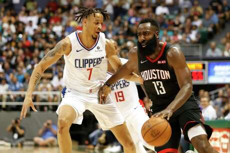 Los Angeles Clippers shooting guard Amir Coffey (7) guards Houston Rockets shooting guard James Harden (13) during the second quarter of an NBA preseason basketball game, Thursday, Oct 3, 2019, in Honolulu. (AP Photo/Marco Garcia)