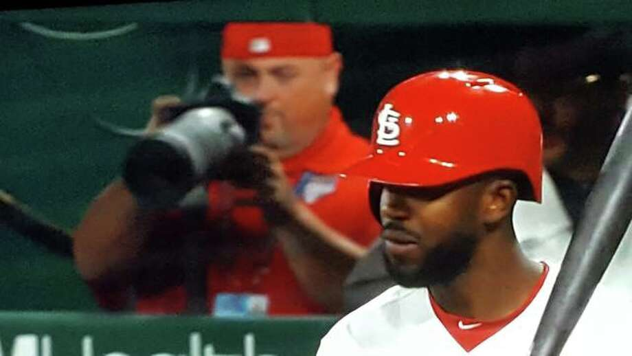 Billy Hurst is seen in the background of a Fox Sports Midwest broadcast setting his camera to Cardinals outfield Dexter Fowler.