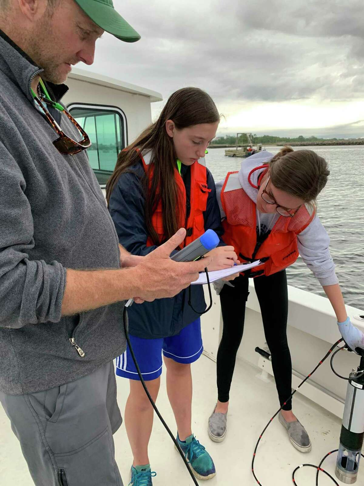 Kevin Blagys, a study volunteer, and students Sienna Matregrano and Charlotte Hickey, check their equipment for testing.