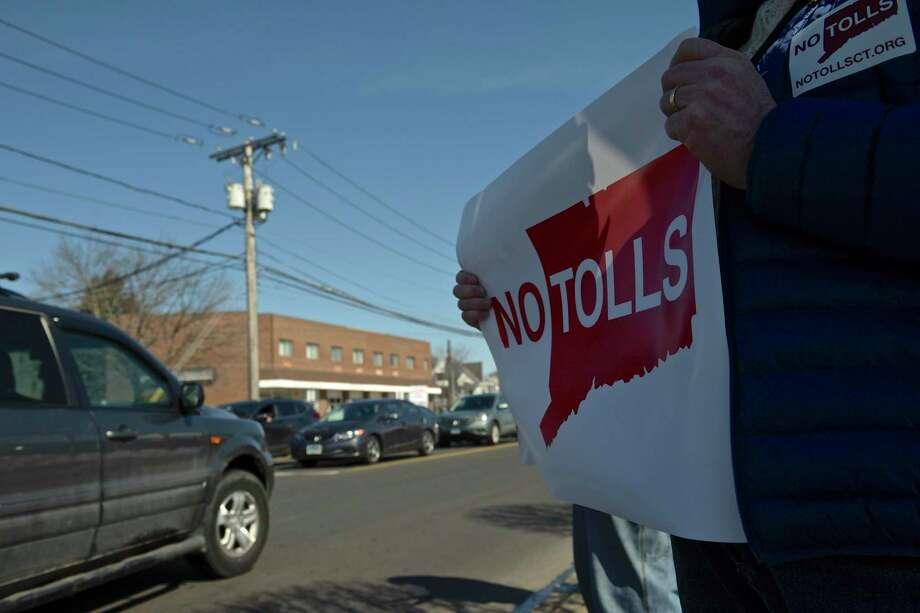 Brian Piper, of Danbury, holds a sign while taking part in an anti-toll protest at the intersection of White and Wildman Streets on Saturday. The protest was organized by Stamford grassroots organization No Tolls Ct. March 9, 2019, in Danbury, Conn. Photo: H John Voorhees III / Hearst Connecticut Media / The News-Times