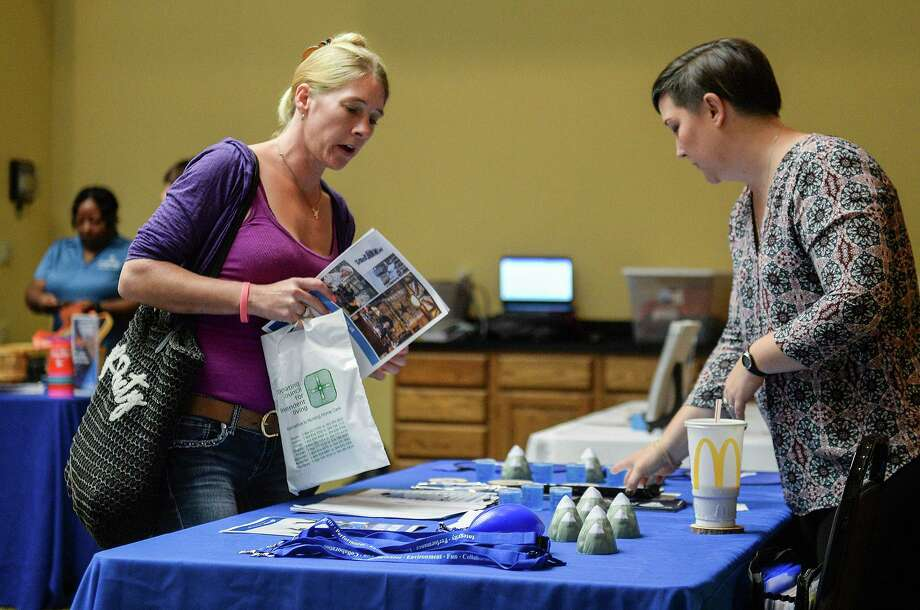 A woman picks up information about a prospective employer at a job fair. Photo: Chris Dorst / Associated Press / Charleston Gazette-Mail