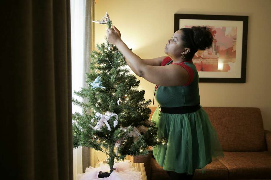 Ajshay James puts her daughter's tiara on an artificial Christmas tree as she decorates a Kingwood hotel room to celebrate the Christmas during a supervised visit. Photo: Elizabeth Conley/Staff Photographer