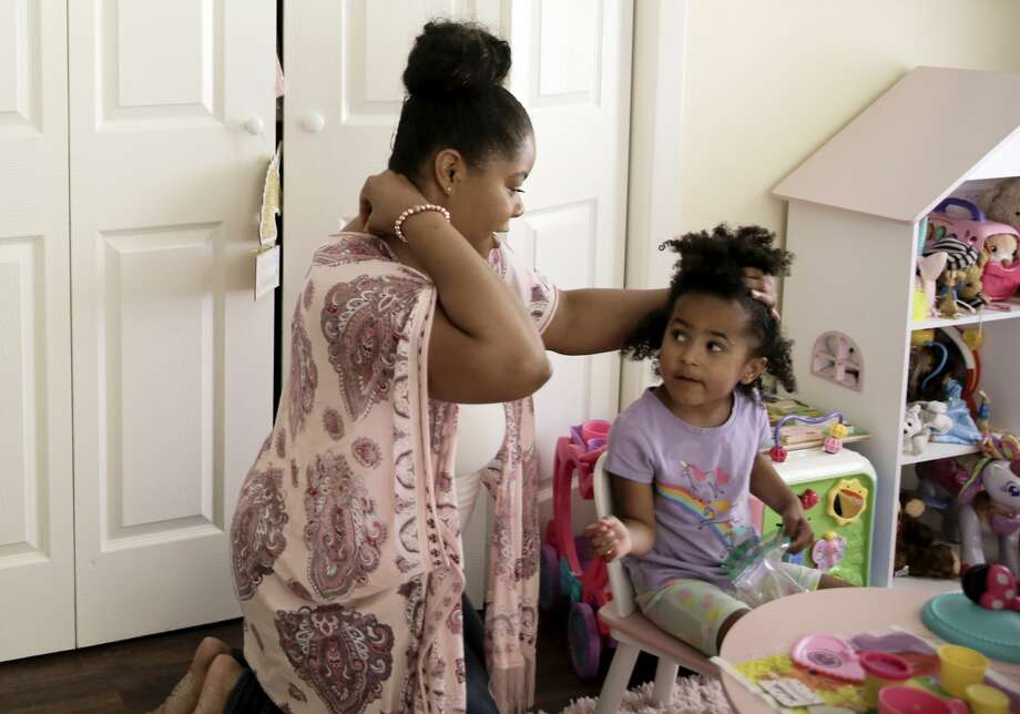 Ajshay James fixes her daughter's hair during one of her scheduled visits. Photo: Elizabeth Conley/Staff Photographer