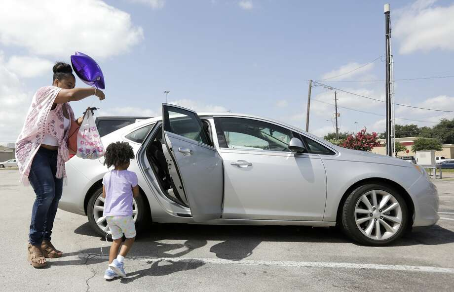 Ajshay James helps her daughter, Harper, back into the car after stopping for ice cream and a balloon during a visit in July. Photo: Elizabeth Conley/Staff Photographer