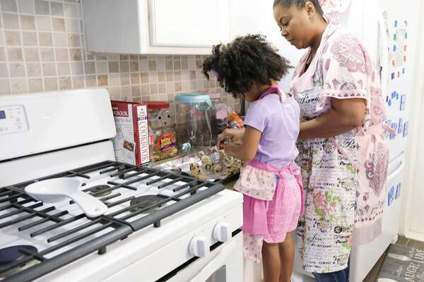 Ajshay James and her daughter, Harper, make cookies during a visit.