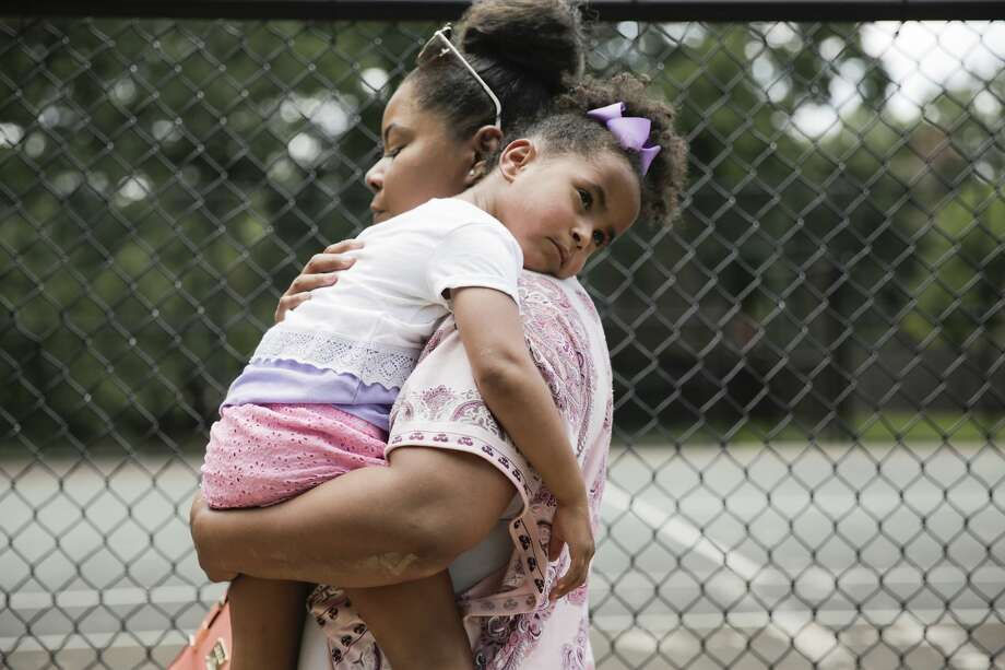 Ajshay James holds her daughter, Harper, in July as they head back to the car to drive back to Harper's paternal grandparents' home. Photo: Elizabeth Conley/Staff Photographer