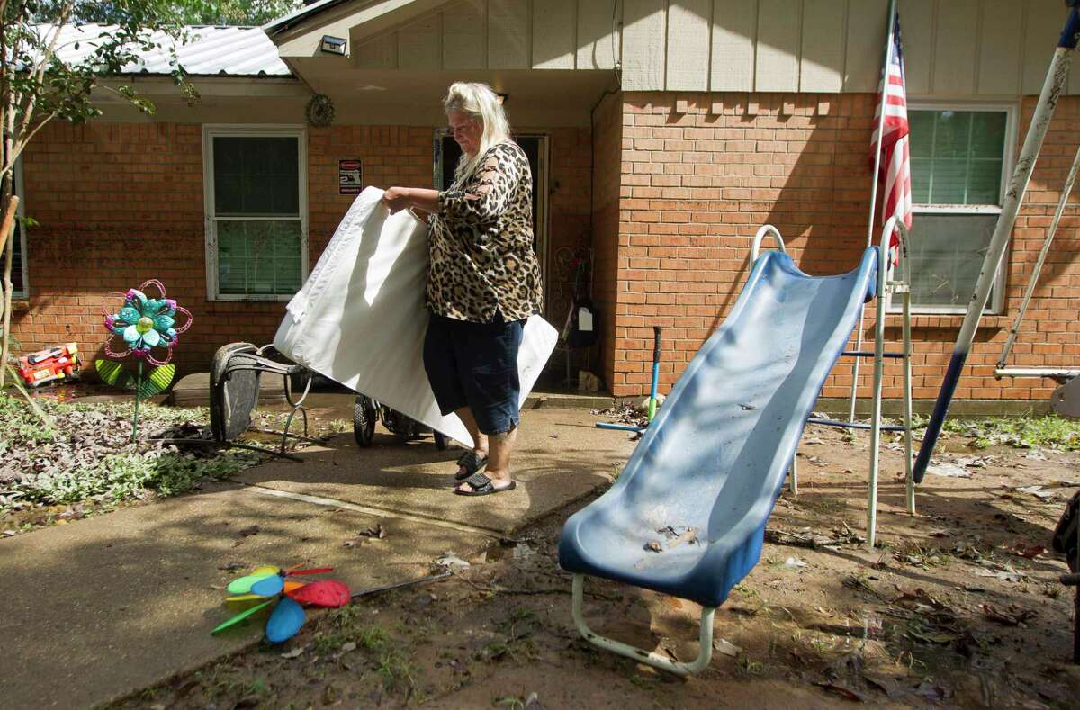 Linda Mason carries a water-logged mattress out of her home after it was flooded with three and a half feet of water from Tropical Depression Imelda, Friday, Sept. 20, 2019, in Splendora.