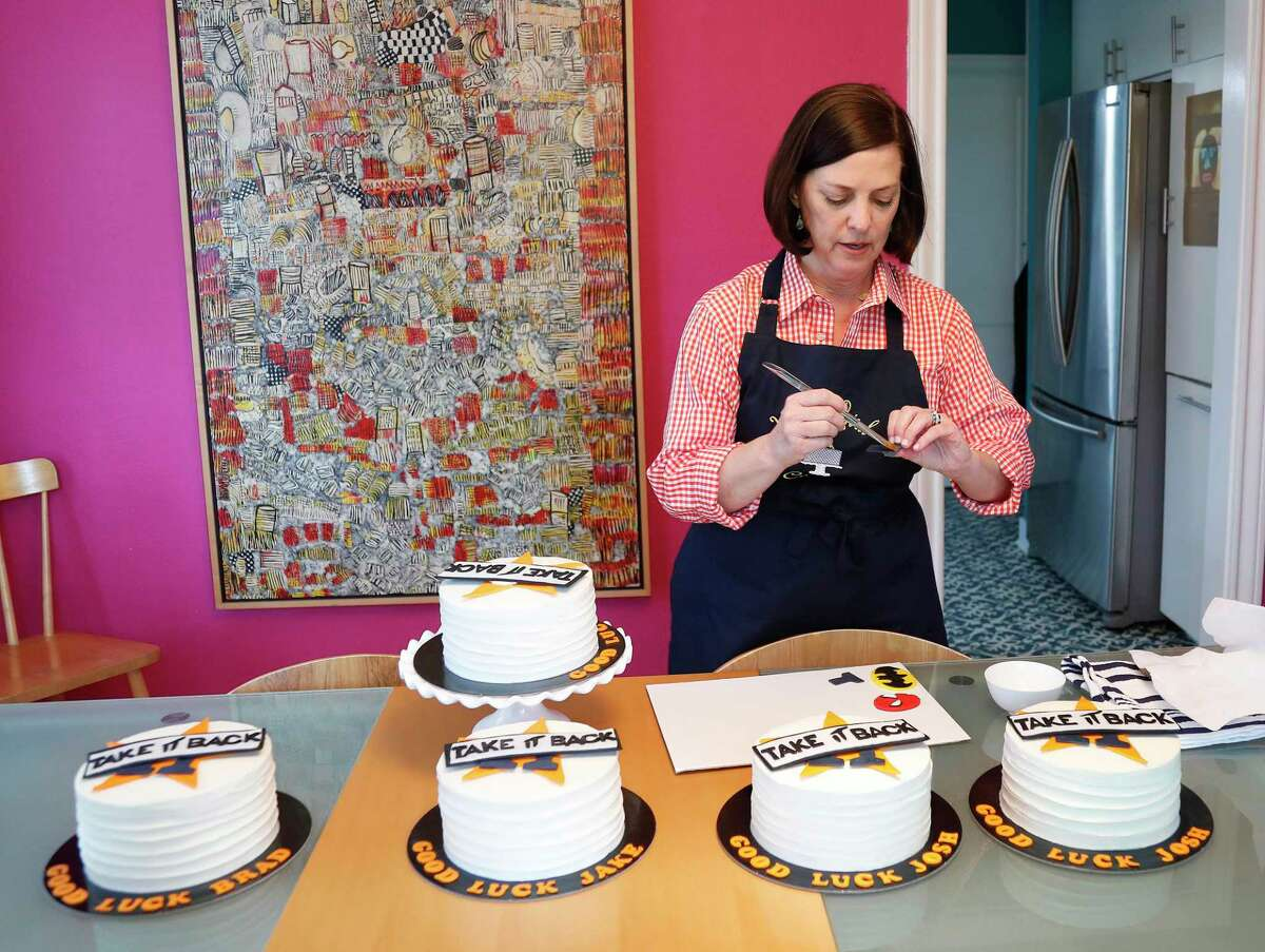 """Janet Roush Flood finishes up the decorating on her """"good luck cakes"""" for several of the Astros players."""