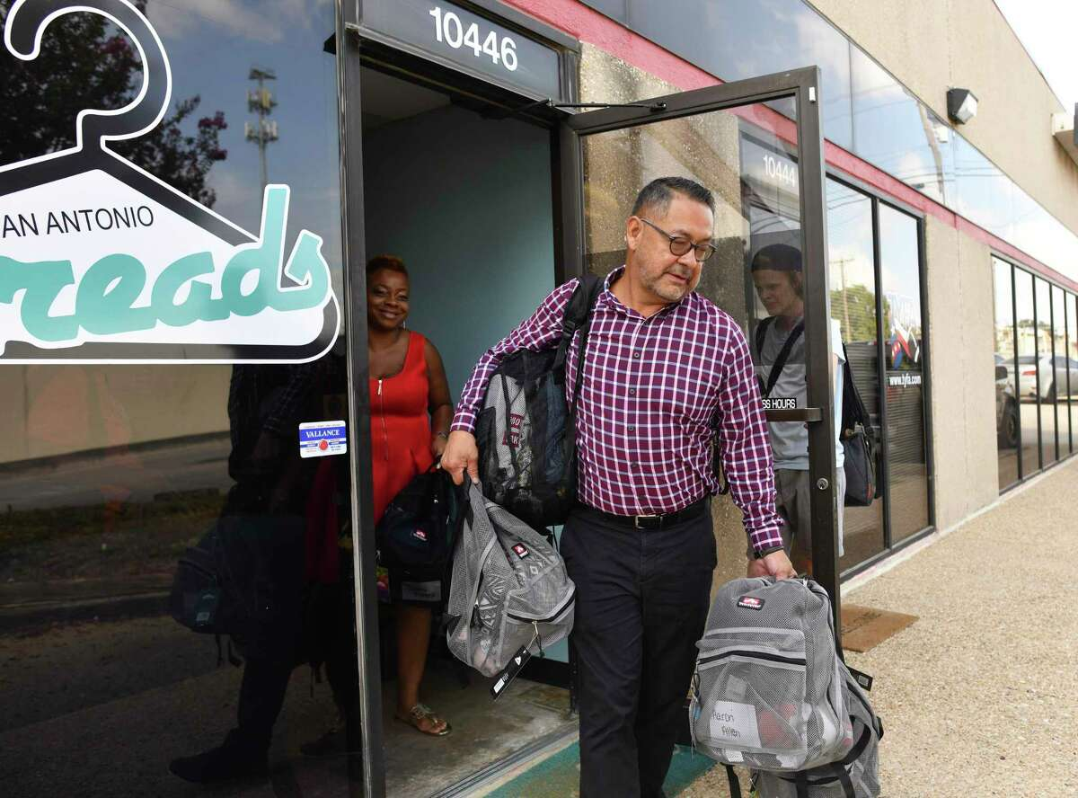 Manuel Ornelas, student services coordinator at Southside ISD picks up backpacks prepared by employees and volunteers at San Antonio Threads on Friday, Aug. 10, 2019. San Antonio Threads, founded by Cathy Hamilton, is a charity where foster and homeless children and teens shop for new, free clothes and shoes.