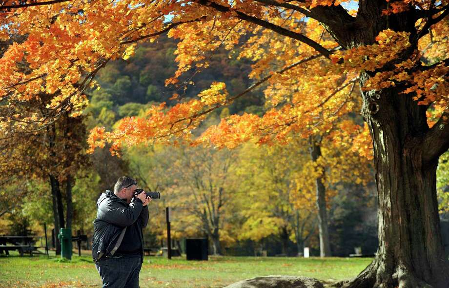 """Dennis Mitchell of Sydney, Australia, stopped at Squantz Pond in New Fairfield on Oct. 24, 2016, to photograph the fall foliage around the state park. He said Sydney has """"pockets"""" of fall colors but """"nothing on the scale of New England."""" Photo: Carol Kaliff / Hearst Connecticut Media / The News-Times"""