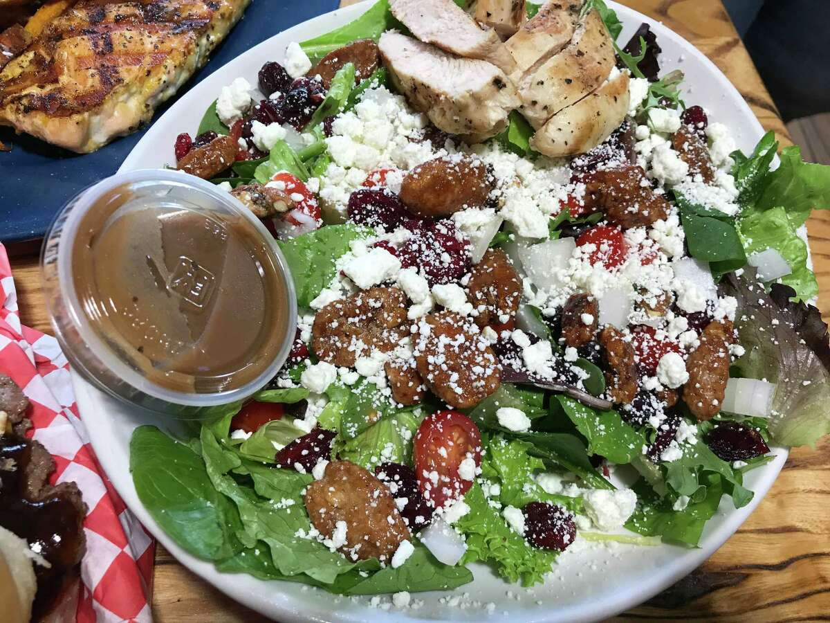The Nutty Goat salad at Dog & Pony Grill includes candied pecans, goat cheese and chicken.