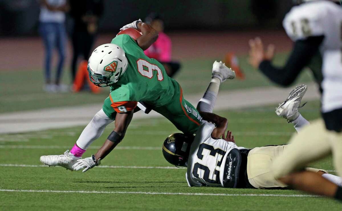 Sam Houston running back Ronald Wilson dives for yardage as he is tackled by Edison Jake Hernandez in the second half of a 5A-1 Region IV District 13 football game . Sam Houston defeated Edison 20-16 at Alamo Stadium on October 3, 2019.