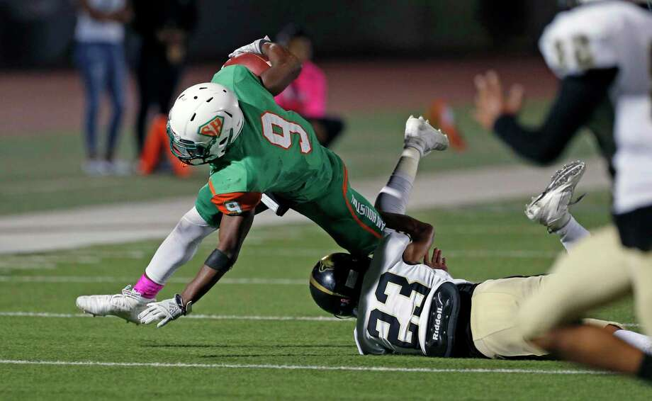 Sam Houston running back Ronald Wilson dives for yardage as he is tackled by Edison Jake Hernandez in the second half of a 5A-1 Region IV District 13 football game . Sam Houston defeated Edison 20-16 at Alamo Stadium on October 3, 2019. Photo: Ronald Cortes/Contributor / 2019 Ronald Cortes
