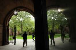 Students walk on Yale's University Old Campus in New Haven Tuesday, October 9, 2012 as seen through Phelps Gate. The mirror reflection at left is a display window that holds a map of Yale's campus. Photo by Peter Hvizdak / New Haven Register