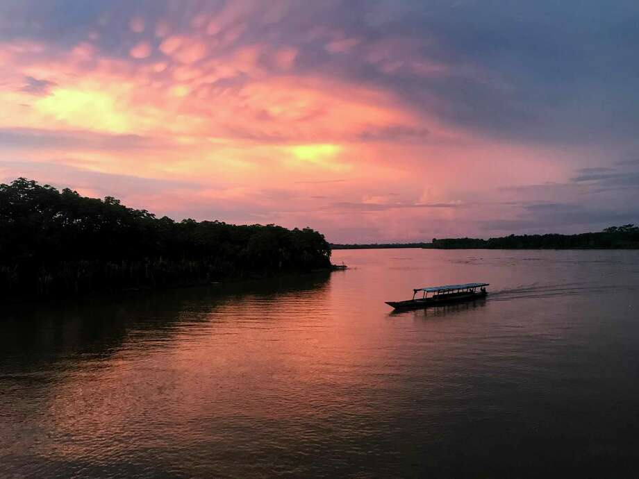 A boat coasts along the Huallaga River at sunset near the Peruvian town of Yurimaguas, the starting point for a trip down the Amazon to Iquitos. Photo: Photo For The Washington Post By Emily Gillespie / Emily Gillespie