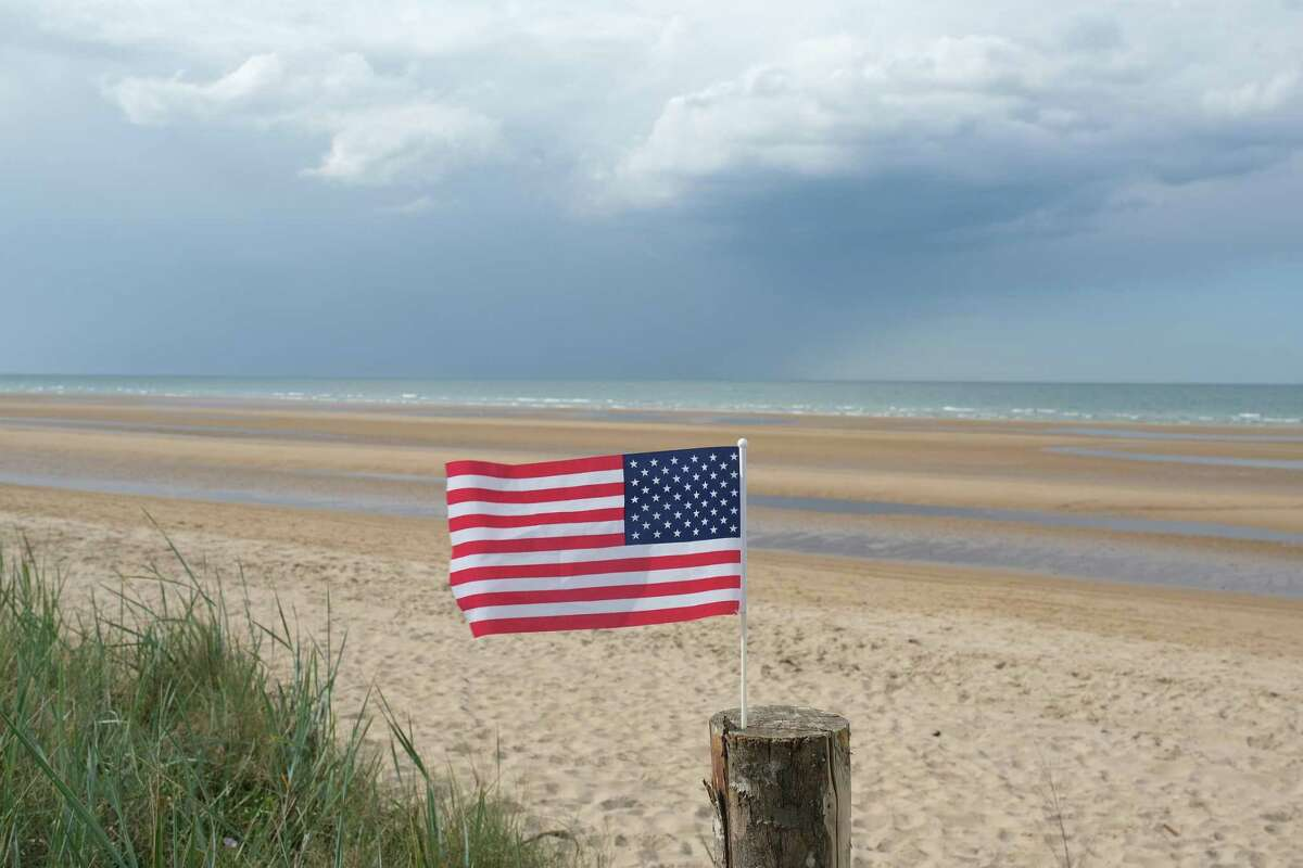 An American flag, likely left by a visitor, flies on Omaha Beach in Normandy on the 75th anniversary of the World War II Allied D-Day invasion on June 6, 2019, near Colleville-Sur-Mer, France.