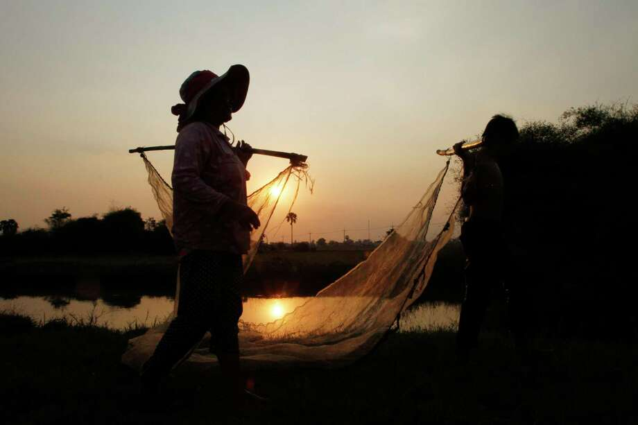 A family prepares a fishing net for catching fish for their evening meal after their day's work in Trapeang Chhouk village in Cambodia. Photo: Heng Sinith, STF / Associated Press / AP