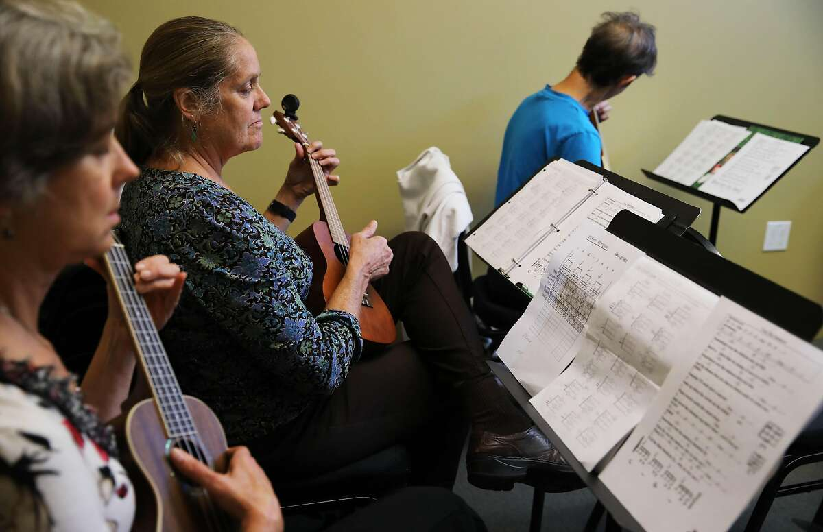Students Lori Tannyhill, left, Anne Bengtson, and Vicky Thomas strum their instruments as Hiram Bell teaches a Beginning Ukulele class at Freight and Salvage in Berkeley, Calif., on Thursday, October 3, 2019. Freight and Salvage offers dozens of classes a year on traditional music. They are reclassifying all the instructors as employees because of California's new gig work law, AB5.