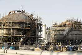 Workers repair damaged tanks at Saudi Aramco's Abqaiq crude oil processing plant following a drone attack in Abqaiq, Saudi Arabia, on Friday, Sept. 20, 2019. Saudi Aramco revealed the significant damage caused by an aerial strike on its Khurais oil field and Abqaiq crude-processing plant last weekend, and insisted that the sites will be back to pre-attack output levels by the end of the month. Photographer: Faisal Al Nasser/Bloomberg
