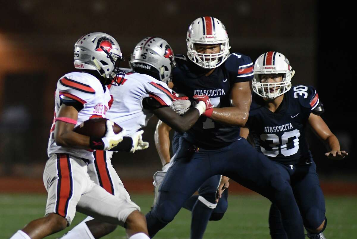 Atascocita senior defensive lineman Asyrus Simon, center, backed up teammate Jack Halm (30), works to stop South Houston sophomore running back Ja'Cory Johnson, left, on a play in the first quarter of their District 22-6A matchup at Turner Stadium in Humble on Oct. 3, 2019.