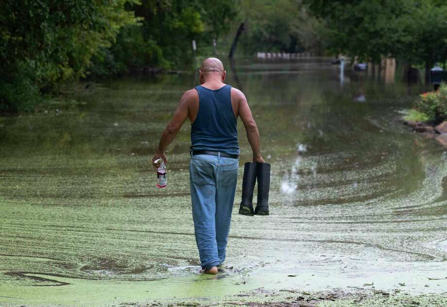 Gabino Hernandez walks a road in Webster covered by overflow from Clear Creek during Tropical Depression Imelda. Webster is participating with other area cities including Dickinson and Friendswood to share costs on an upcoming $1.5 million flood-control study for the lower sections of Clear Creek and for Dickinson Bayou. Photo: Stuart Villanueva, MBR / Associated Press / © 2019 Stuart Villanueva/The Galveston County Daily News