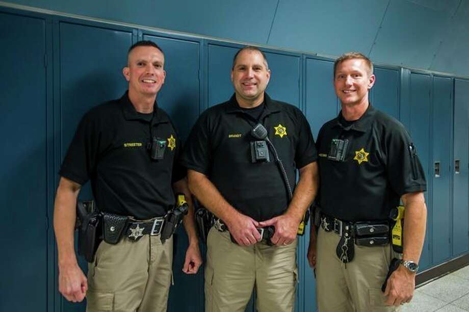 From left, School Resource Officers Jodye Streeter, who works at Meridian Early College High School, Jason Brandt, who works at Bullock Creek High School, and Brandan Hodges, who works at Coleman High School, pose for a portrait Friday at Meridian Early College High School. (Katy Kildee/kkildee@mdn.net)