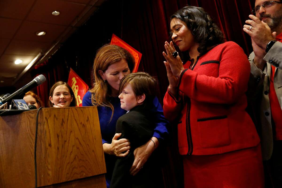 Suzy Loftus (third from left), interim district attorney, kisses her daughter Grace Loftus (third from right) during a press conference at Far East Cafe after Mayor London Breed (second from right) announced the appointment of Suzy Loftus as interim district attorney on Friday October 4, 2019 in San Francisco, Calif. Loftus' other two daughters Maureen Loftus (left), 14 and Vivienne Loftus (second from left), 12 applaud as they stand with their mother.