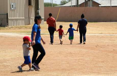Immigrants seeking asylum hold hands as they walk across the ICE South Texas Family Residential Center, Friday, Aug. 23, 2019, in Dilley, Texas. U.S. Immigration and Customs Enforcement hosted a media tour of the center that houses families who are pending disposition of their immigration cases.