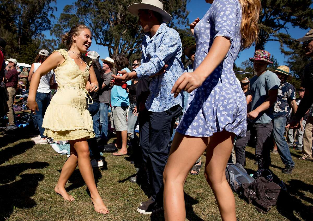 A young woman who declined to be identified enjoys the music, sunshine and vibe barefoot in the grass while attending the opening afternoon of Hardly Strictly Bluegrass music festival at Hellman Hollow in Golden Gate Park, San Francisco, Calif. on Friday, October 4, 2019