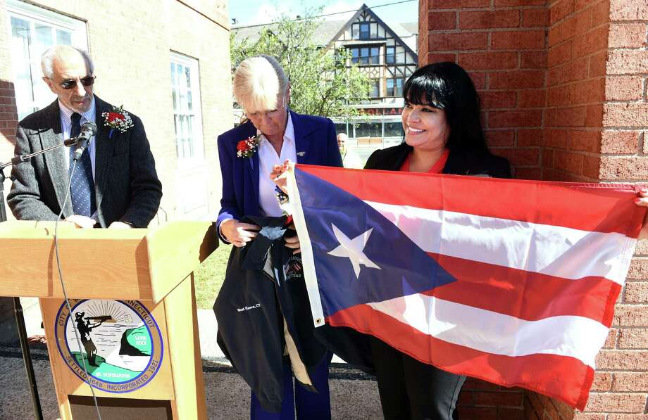West Haven Hispanic American of the Year Iris Milagros Diaz, right, receives the Puerto Rican flag from Mayor Nancy Rossi, center, in front of City Hall in West Haven Friday. At left is Louis Esposito, executive assistant to Mayor Rossi. Photo: Arnold Gold / Hearst Connecticut Media / New Haven Register