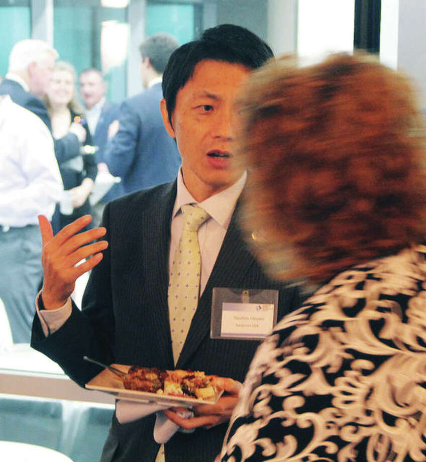 Yasuhiro Uozumi, executive director of Keidanren USA, talks to Leadership Council Southwestern Illinois Executive Director Ronda Sauget during a reception for Uozumi and other Japanese economic development officials who toured the Metro East and St. Louis area Thursday and Friday.