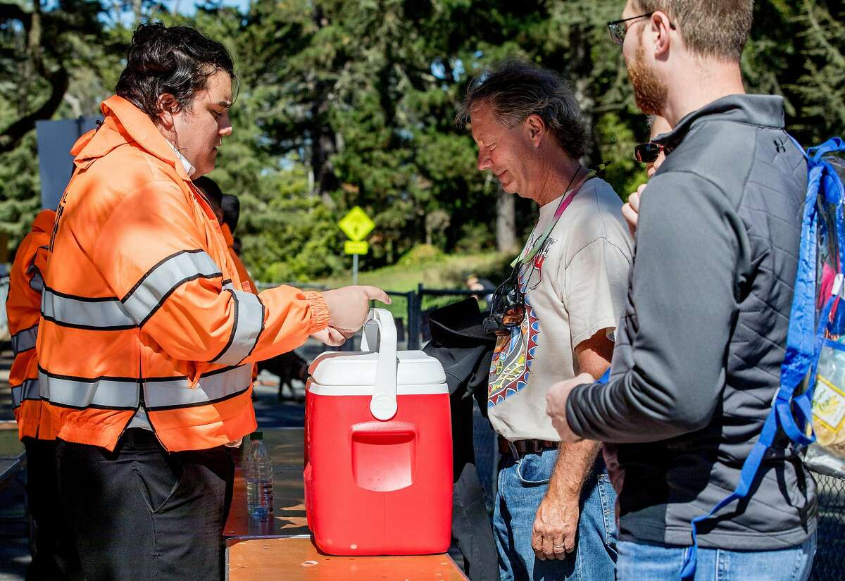 Mitch Popa of Idaho lifts his cooler to be checked in a security line during the Hardly Strictly Bluegrass Festival held at Golden Gate Park in San Francisco, Calif. Friday, Oct. 4, 2019. According to new security rules for the festival, coolers were supposed to have been banned.