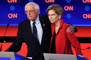 In this file photo taken on July 30, 2019, Democratic presidential hopefuls Sen. Bernie Sanders (I-Vt.), left, and Sen. Elizabeth Warren (D-Mass.) after participating in the first round of the second Democratic primary debate of the 2020 presidential campaign season in Detroit. (Brendan Smialowski/AFP/Getty Images/TNS)