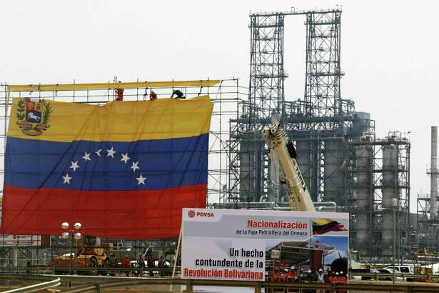 Oil workers hang a Venezuelan flag at the Jose Complex during celebrations in Barcelona, Venezuela, May 1, 2007, as the state-run oil company PDVSA takes control of oil fields in the Orinoco Belt. Venezuela stripped the world's biggest oil companies of operational control over massive Orinoco Belt crude projects on Tuesday, a vital move in President Hugo Chavez's nationalization drive. REUTERS/Jorge Silva (VENEZUELA)