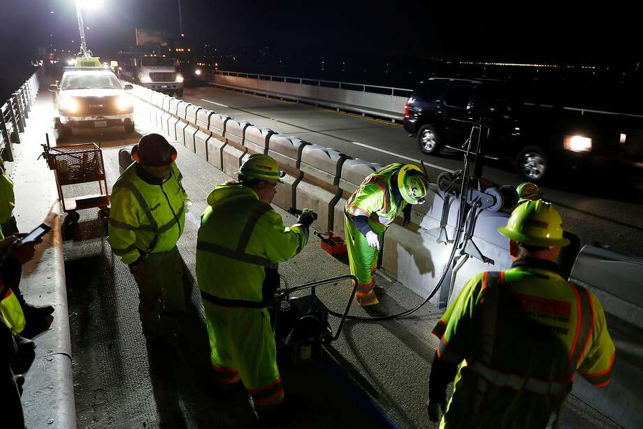 Workers install a movable barrier for the bike and pedestrian lane on the Richmond-San Rafael Bridge. Photo: Photos By Scott Strazzante / The Chronicle