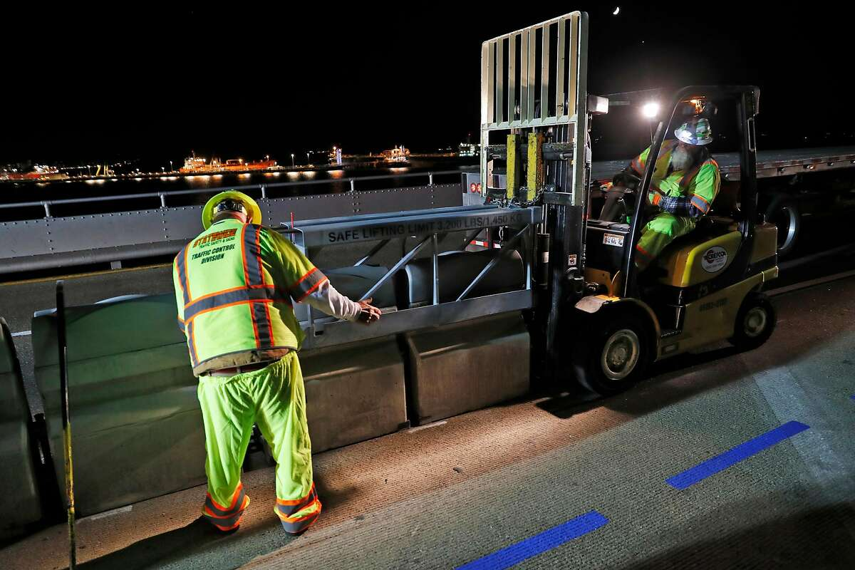 Workers install movable barrier for the long-awaited bike and pedestrian path along the right shoulder of the upper deck of the Richmond-San Rafael Bridge in Richmond, Calif., on Thursday, October 3, 2019.