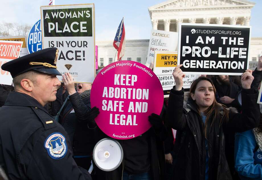 """(FILES) In this file photo taken on January 18, 2019 pro-choice activists hold signs alongside anti-abortion activists participating in the """"March for Life,"""" an annual event to mark the anniversary of the 1973 Supreme Court case Roe v. Wade, which legalized abortion in the US, outside the US Supreme Court in Washington, DC. - (Photo by SAUL LOEB / AFP) (Photo by SAUL LOEB/AFP via Getty Images) Photo: Saul Loeb, AFP Via Getty Images"""
