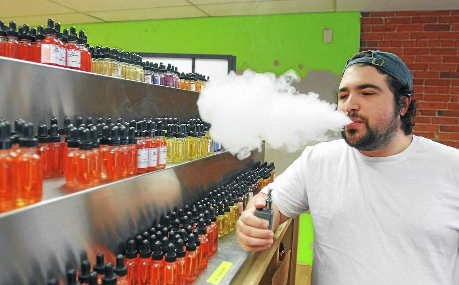 Noah Morgenstein, of the White Buffalo Vape shop, stands near the store's selection of flavors in 2014. The store has a policy to card everyone who looks even remotely young to verify that they are at least 18-years-old. 5/03/14 pcasolino@newhavenregister.com Photo: Hearst Connecticut Media File Photo