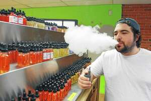Noah Morgenstein, of the White Buffalo Vape shop, stands near the store's selection of flavors in 2014. The store has a policy to card everyone who looks even remotely young to verify that they are at least 18-years-old. 5/03/14 pcasolino@newhavenregister.com