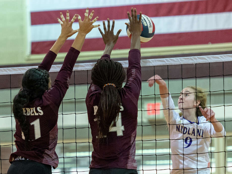 Midland High's Madelyn Kennedy (9) hits the ball into Lee's Yali Flores (11) and Loredana Fouonji (14) block on Friday, Oct. 4, 2019 at Lee High School gym. Photo: Jacy Lewis/Reporter-Telegram