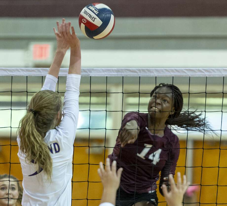 Lee's Loredana Fouonji (14) hits the ball off of Midland High's Madelyn Kennedy's (9) block Friday, Oct. 4, 2019 at Lee High School gym. Photo: Jacy Lewis/Reporter-Telegram