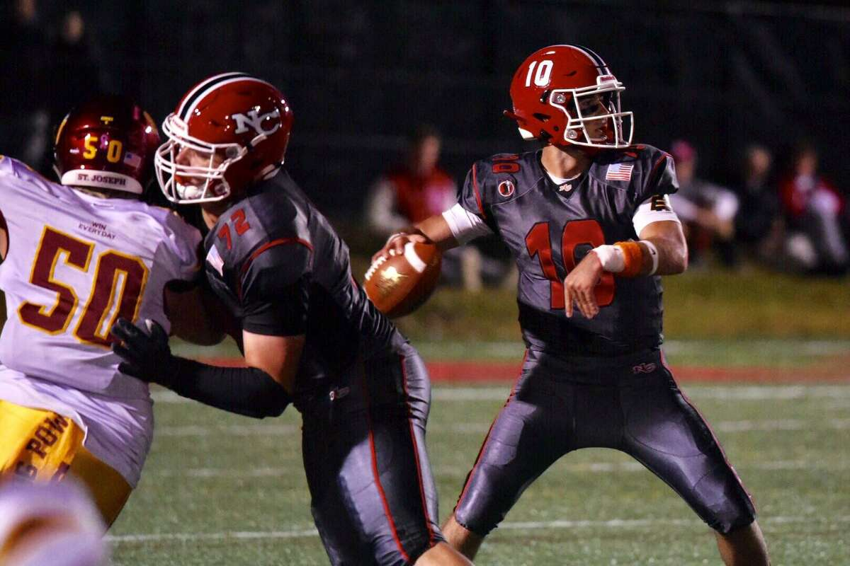 New Canaan's Drew Pyne throws a pass while Ben Clay blocks during the Rams' 58-14 loss to St. Joseph on Friday at Dunning Field.