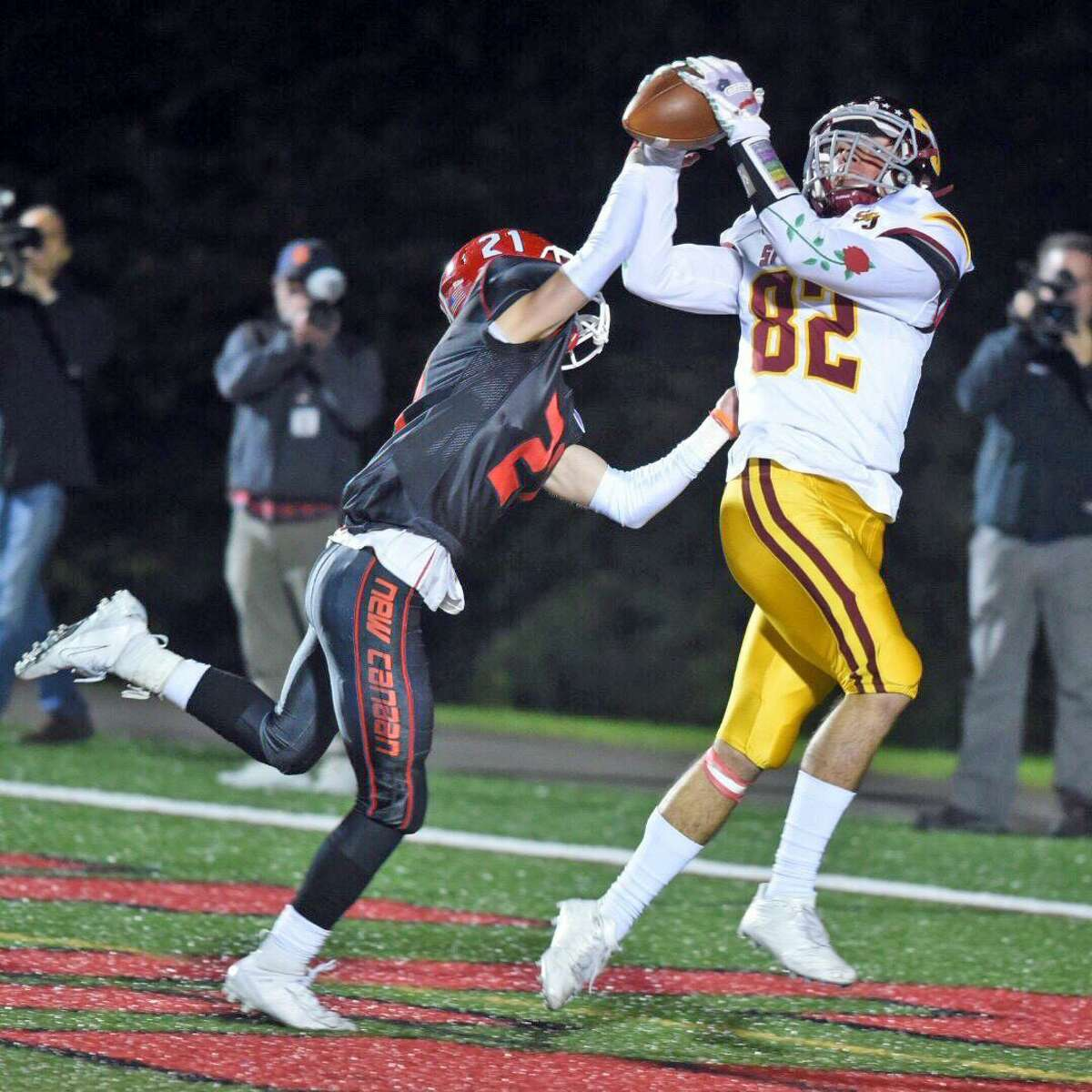 St. Joseph's Will Diamantis catches a touchdown pass from Jack Wallace with New Canaan's Dean Ciancio defending during the Cadets' 58-14 victory on Friday at Dunning Field in New Canaan.