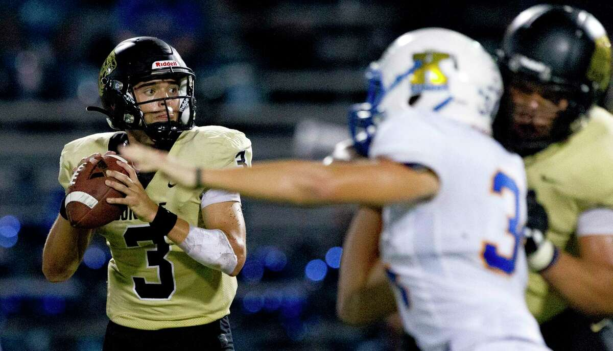 Conroe quarterback Christian Pack (3) looks to pass under pressure during the fourth quarter of a District 15-6A high school football game at Buddy Moorhead Stadium, Friday, Oct. 4, 2019, in Conroe.