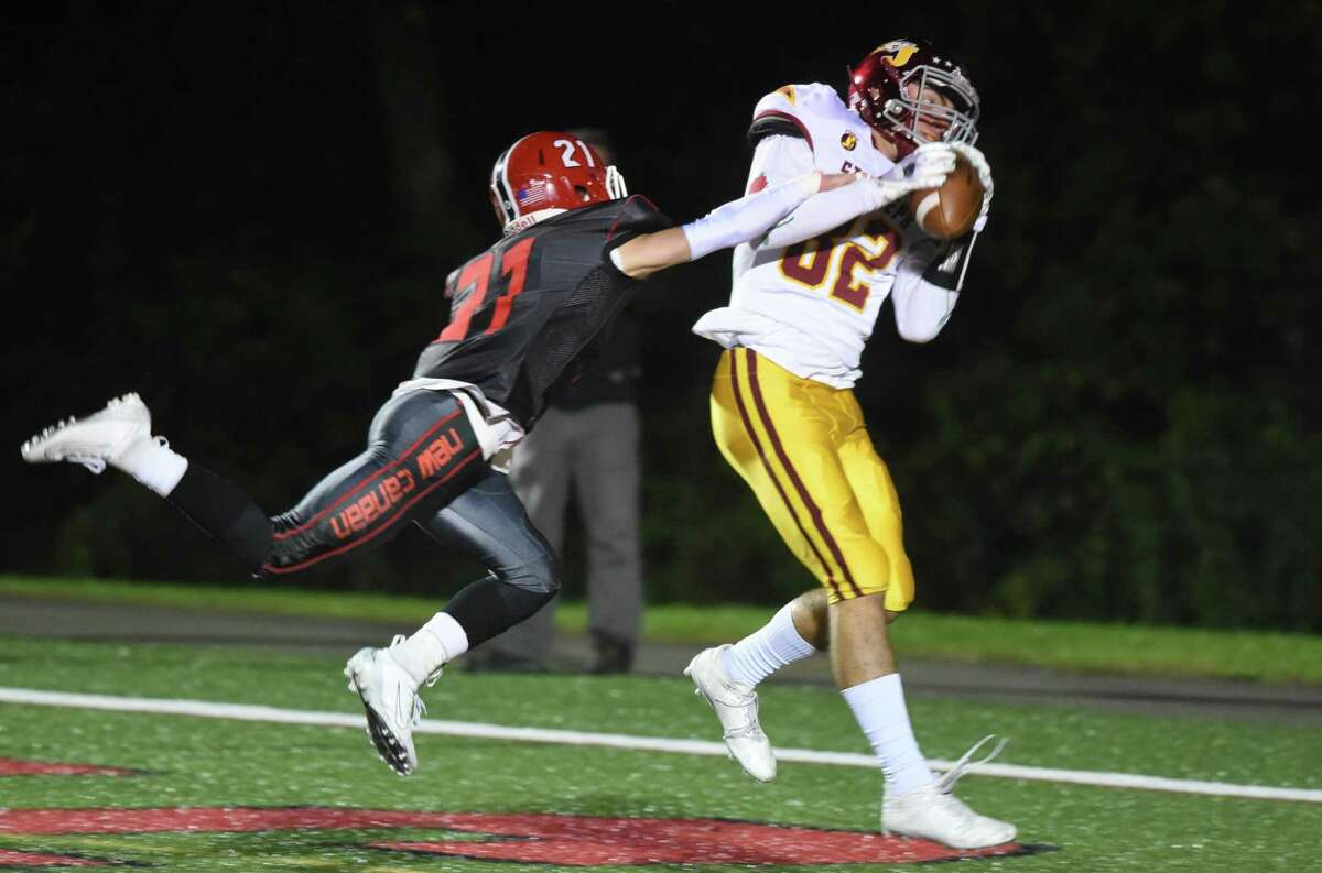 St. Joseph's Will Diamantis (82) catches a touchdown pass from QB Jack Wallace with New Canaan's Dean Ciancio (21) defending during a football game at Dunning Field on Friday, Oct. 4, 2019.