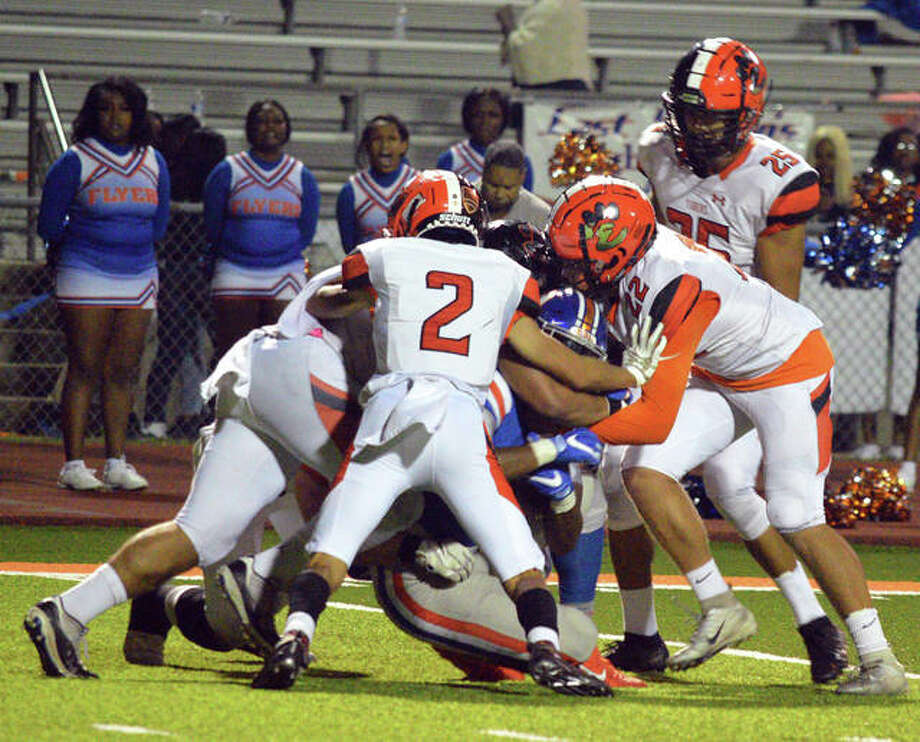 The Edwardsville defense tackles an East St. Louis player during the second quarter of Friday's Southwestern Conference game at East St. Louis. Photo: Scott Marion|Intelligencer