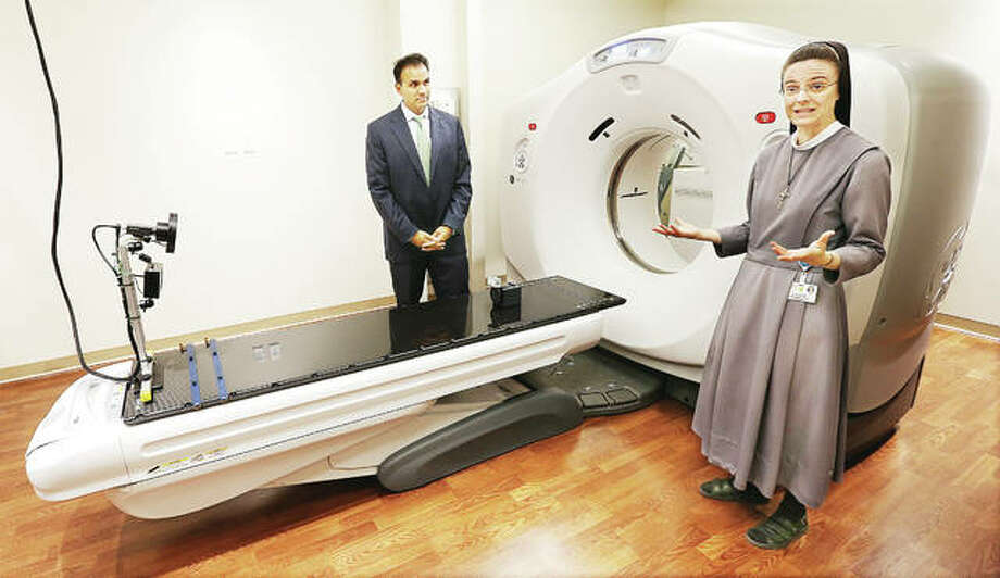 Sister M. Anselma, chief operating officer at OSF Saint Anthony's Health Center in Alton, talks about the new Moeller Cancer Center at the Alton hospital as she stands in front of a CT scanner in the new facility with Ajay Pathak, president and CEO of the health center, left. The $14 million state of the art cancer treatment building will have a public blessing and dedication from 3-3:45 p.m. Tuesday followed by an open house. Madison County has the second highest rate of cancers in Illinois. Photo: John Badman | The Telegraph