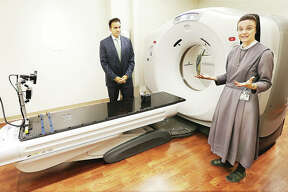 Sister M. Anselma, chief operating officer at OSF Saint Anthony's Health Center in Alton, talks about the new Moeller Cancer Center at the Alton hospital as she stands in front of a CT scanner in the new facility with Ajay Pathak, president and CEO of the health center, left. The $14 million state of the art cancer treatment building will have a public blessing and dedication from 3-3:45 p.m. Tuesday followed by an open house. Madison County has the second highest rate of cancers in Illinois.